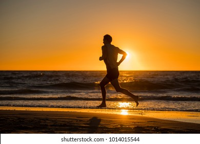 silhouette of young dynamic athlete runner man with fit strong body training on beautiful Summer sunset beach sand running barefoot in sport well being and healthy lifestyle concept