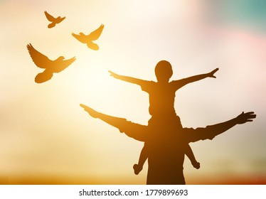 Silhouette of young family and free birds fly