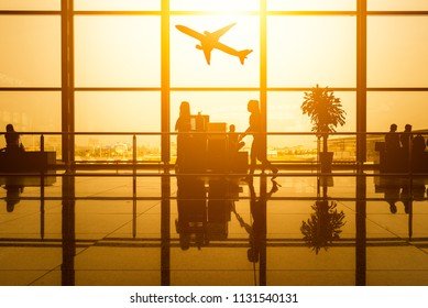Silhouette of young family with luggage walking at airport,