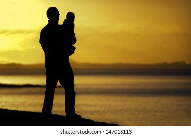 Silhouette of a young father carries his child on the beach during sunset.  Concept photo of fathers day, parenting, fatherhood, love, care,  single father.