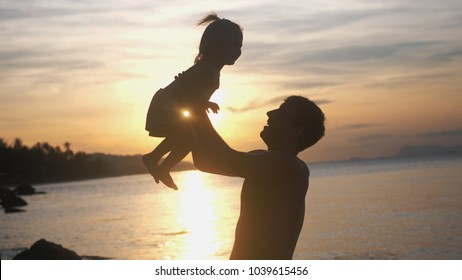 Silhouette of young father and daughter spending happy time at beach during sunset