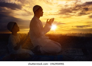 Silhouette of young father with his son praying to the Allah after doing Salat while sitting together on the hill at sunset time - Shutterstock ID 1962904981