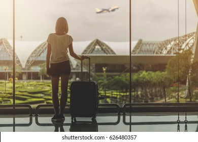 Silhouette of the young female tourist with a bag standing near the window at the airport and looking at the garden outside while waiting for check in. Mock up, copy space for your text.