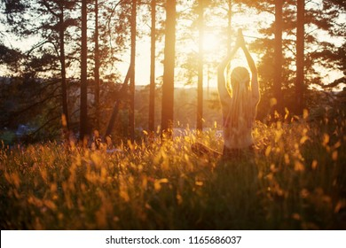 Silhouette of Young female wearing long hair dreadlocks seating in forest outdoor, doing yoga meditation on sunset