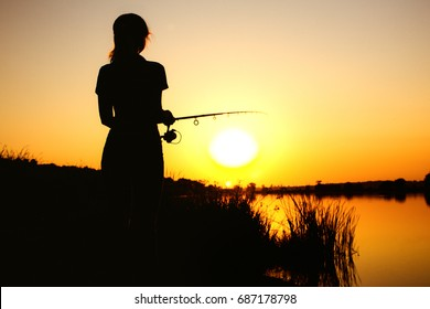 Silhouette of a young fishing woman on the river bank in the reeds resting on the nature at dawn