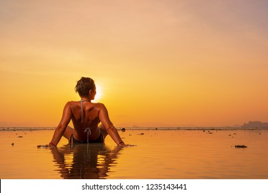 Silhouette of a young and fit woman on the beach at sunset