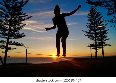 Silhouette of a young girl balancing on a slackline in the open air between two trees at sunset at scarborough beach in Perth, Australia.