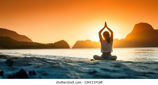Silhouette of young girl doing yoga at sunset time. Meditation concept