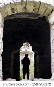 Silhouette of young girl in the doorway of dilapidated ancient synagogue.View through an arched window. Rashkov, Moldova. Close-up. Selective focus.