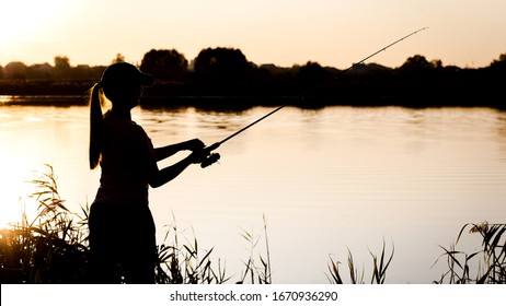 Silhouette of a young girl with a fishing rod on the river Bank.