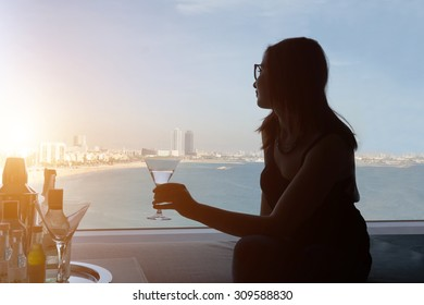 Silhouette of young girl holding a cocktail and sitting on the sofa in her suite hotel room while looking through big window a beautiful beach views - woman take a journey in luxury hotel with seaside