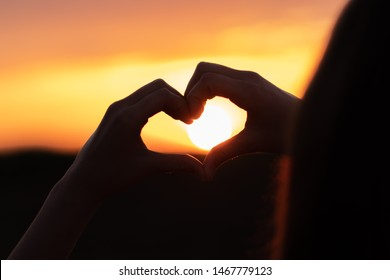 Silhouette of a young girl holding sun in her hands shaped like heart at sunset