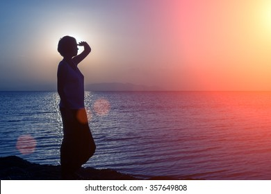 Silhouette of young girl looking into the distance, standing on the beach, at the sunset against the sun