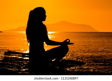 Silhouette of young girl meditating at the morning sunrise on the coast of Red sea in yoga pose