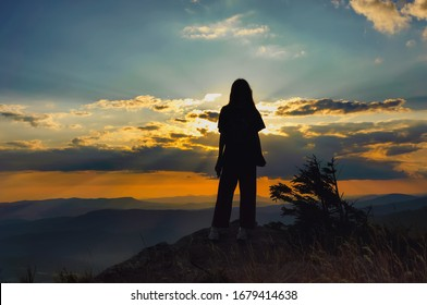 Silhouette of a young girl on a background of beautiful sunset in the mountains