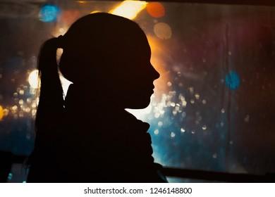 Silhouette of young girl on night city bokeh background. Rain drops running down the window. Autumn season