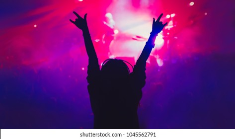 Silhouette of young girl partying on concert in night club.Music hall background.Young woman put hands up to the music with rock on gesture.Rock and roll concert audience.