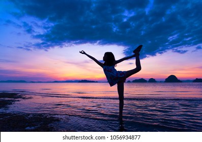 Silhouette of young girl practicing Yoga Warrior pose on tropical beach with sunset sky background. Healthy  teenage woman lifestyle balanced practicing meditate and energy yoga. Healthy life Concept.