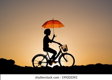 Silhouette of Young girl riding a bicycle  holding a red umbrella.