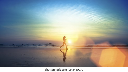 Silhouette of a young girl running along the beach of the sea during an amazing sunset.