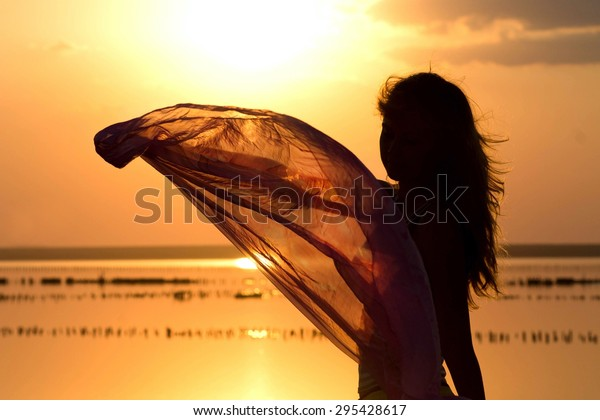 silhouette of a young girl with a shawl