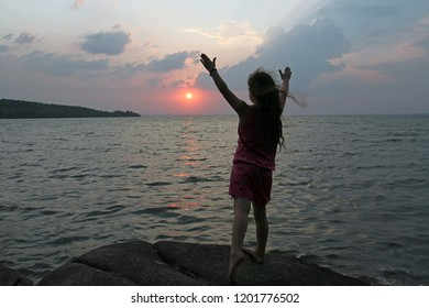 Silhouette of a young girl standing on the background of the sunset and the sea with outstretched arms