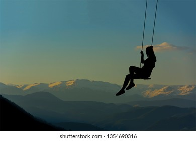 silhouette - young girl swinging in the sunset