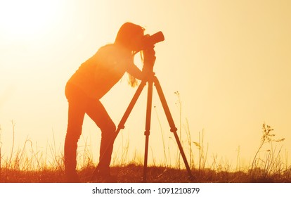 Silhouette of a young girl who is taking pictures. Girl photographer with camera at the countryside at sunset time