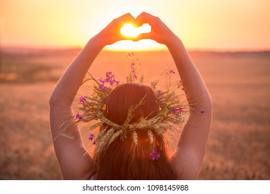 Silhouette of young girl with wreath on head standing at wheat field making heart symbol with his hands at sunset