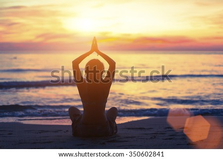 Silhouette of young girl in yoga pose sitting on the beach during sunset.