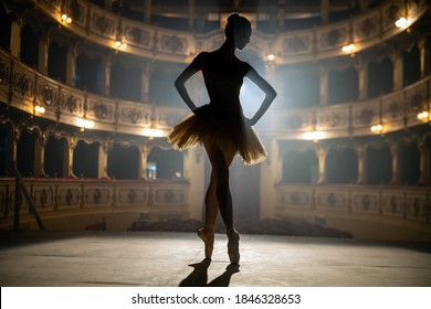Silhouette of a young graceful classical ballet female dancer in white tutu is performing a choreography on classic theatre stage with dramatic lighting before start of a show.