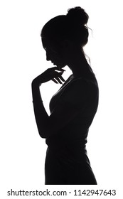 silhouette of a young graceful woman with hand near chin, profile of a beautiful girl on a white isolated background, concept life and problems