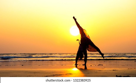 Silhouette of young gymnast woman doing handspring on sandy beach at beautiful orange sunset.