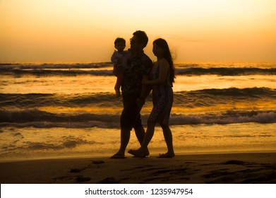silhouette of young happy and beautiful Asian Chinese couple holding baby girl daughter walking on sunset beach enjoying together romantic summer holidays trip and family sweet vacations