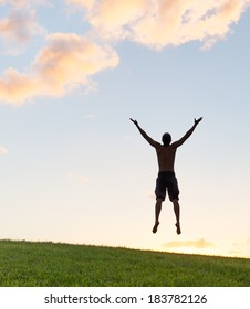 Silhouette of young happy man jumping in the park. Enjoyment. Freedom concept.