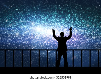 Silhouette of young happy man stands on the bridge in cosmos