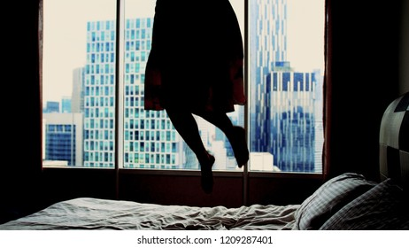 Silhouette of young happy woman in dress jumping on hotel bed.