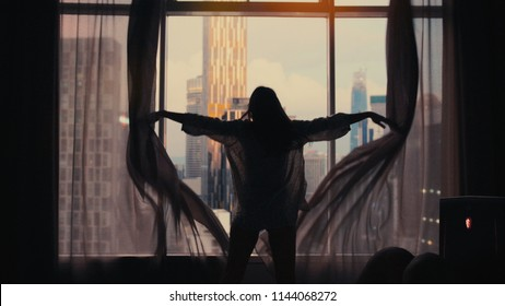 Silhouette of young happy woman opening window curtains on buildings on the background