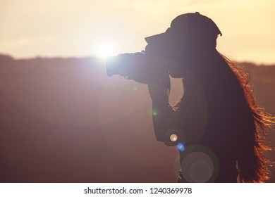 Silhouette young Hipster girl photographer taking Photo in Top peak mountain at sunrise Travel adventure in Destination. Nature Explore, outdoor mountain traveling. Travel red hair woman at Sun.