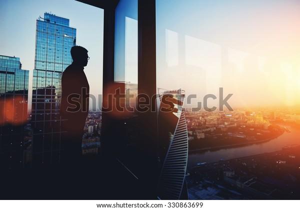 Silhouette de joven hombre inteligente director gerente descansando después de una reunión de negocios tardía mientras se encuentra cerca del fondo de la ventana de la gran oficina con espacio para copiar su mensaje de texto o contenido promocional