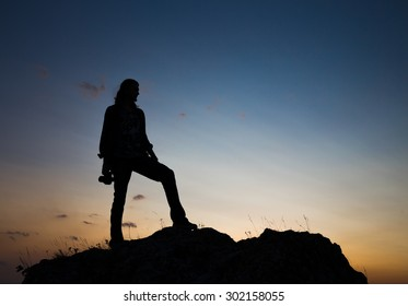 Silhouette of young longhair male model with dslr camera at blue and yellow sunset.