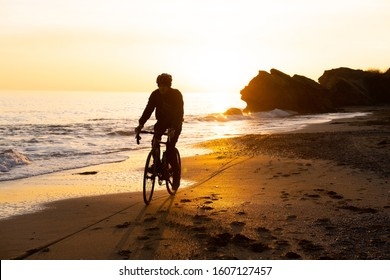 silhouette of young male bicycle rider in helmet on the beach during beautiful sunset