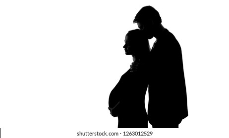 Silhouette of young male kissing sad pregnant woman, unhappy relationship