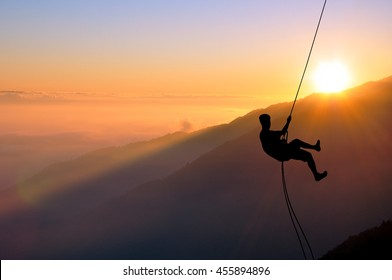 Silhouette of young man abseiling down from a cliff, sun, beautiful colorful sky and clouds behind. Climber rappelling from a rock during sunset.