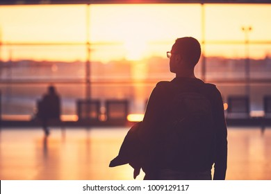 Silhouette of the young man at the airport. Traveler leaves to the gate during golden sunset.