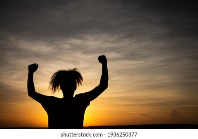 Silhouette of a young man with arms raised during sunset. sign of joy or victory. Curly hair on a man. vacation landscape.