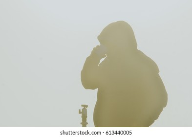 Silhouette of Young man with backpack taking a photo on the top of mountains