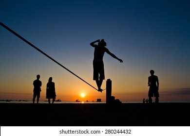 Silhouette of young man balancing jumping on slackline during sunset at a beach in Manabi