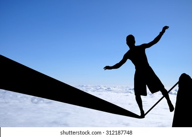 Silhouette of young man balancing on slackline high above clouds. Slackliner balancing on tightrope, highline silhouette.