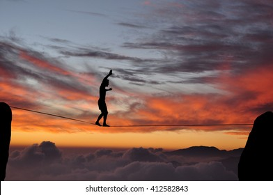 Silhouette of young man balancing on slackline high above clouds and mountains during sunset. Slackliner balancing on tightrope between two rocks sun and clouds behind, highline silhouette.